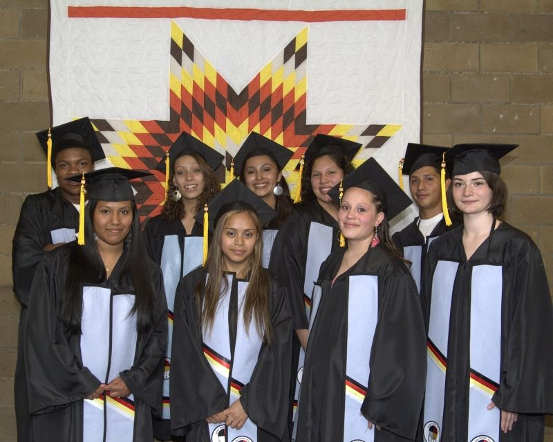 Nine Indigenous students wearing caps and gowns